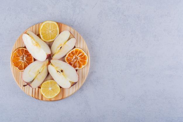 Placa de madera de manzanas frescas y rodajas de limón sobre la mesa de piedra.
