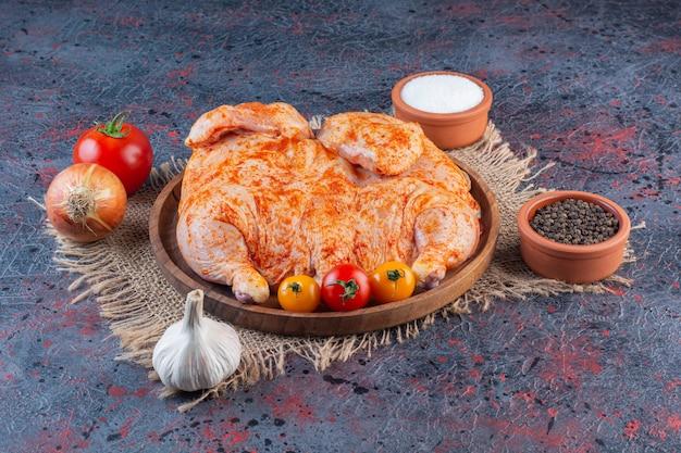 Placa de madera de pollo entero marinado sobre superficie de mármol.