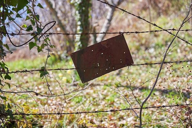 Placa de metal oxidado viejo colgando de un alambre de púas