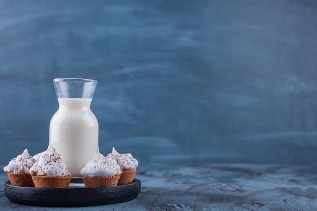 Placa negra con dulces cupcakes cremosos y vaso de leche sobre fondo de mármol.