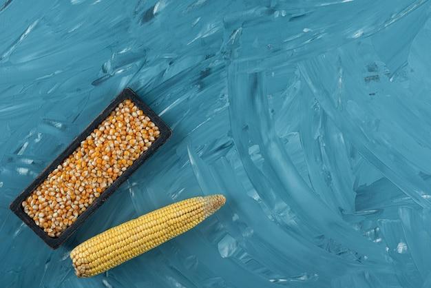 Placa negra de granos de maíz crudo sobre fondo azul.