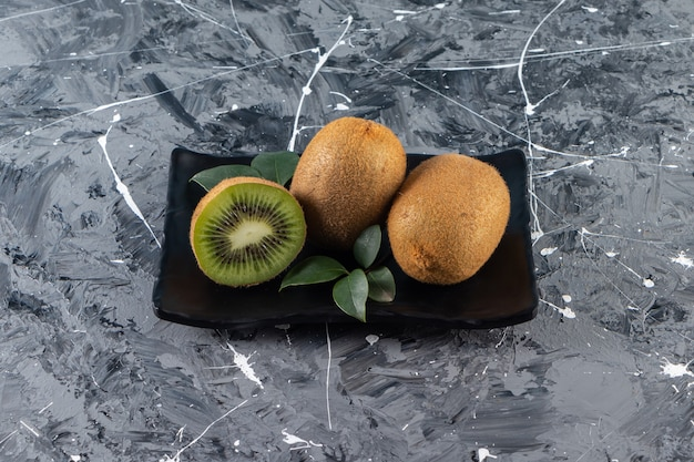 Placa negra de kiwis enteros colocados sobre una mesa de mármol.