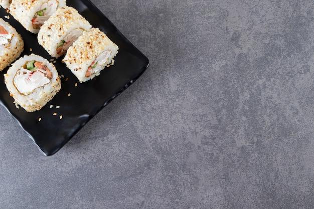 Placa negra de rollos de sushi con semillas de sésamo sobre fondo de piedra.