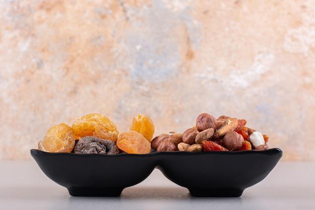 Placa oscura de diversos frutos secos orgánicos sobre fondo blanco. foto de alta calidad