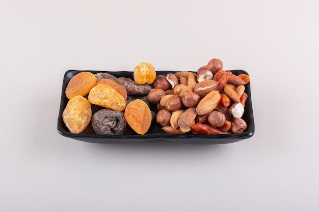 Placa oscura de diversos frutos secos orgánicos sobre superficie blanca. foto de alta calidad