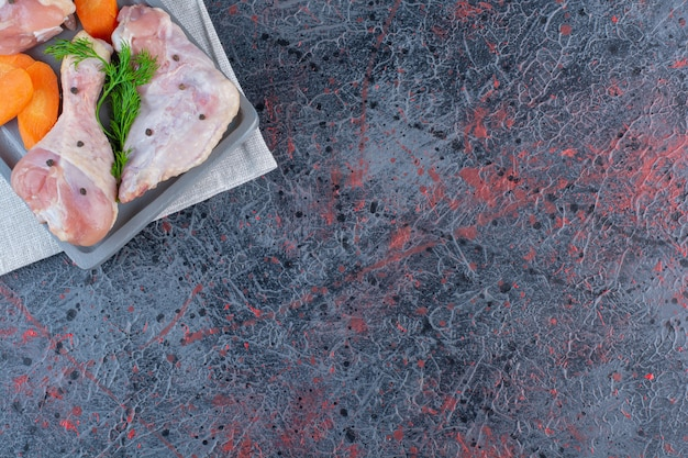 Placa oscura de muslos de pollo crudo sobre superficie de mármol