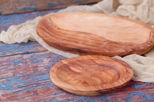 Placa ovalada de madera sobre un fondo de tablas viejas.