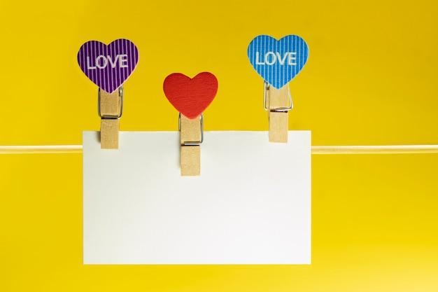 Placa de papel blanco con espacio para texto con pinzas para la ropa en forma de corazón en un cordón. fondo amarillo brillante. mock ap. día de san valentín.