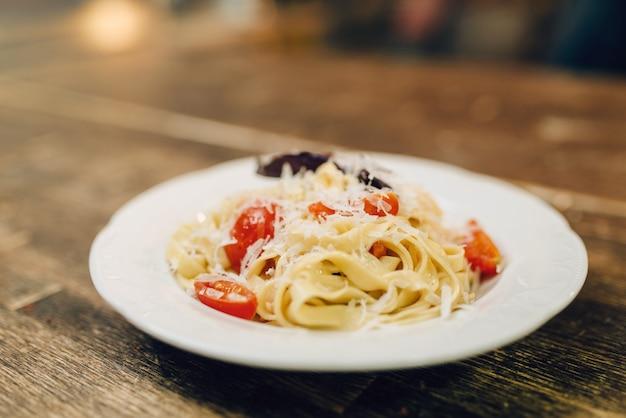 Placa con pasta fresca cocida en primer plano de la mesa de madera, nadie. fettuccine casero, comida sana. cocina tradicional italiana