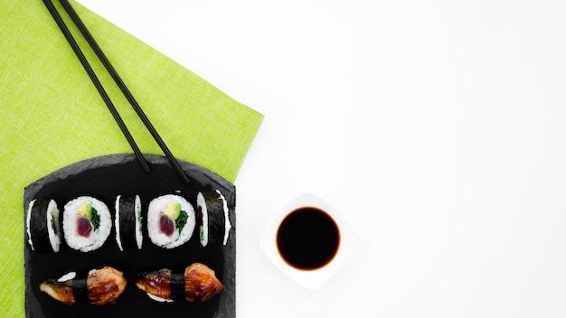Placa de piedra negra con rollos de sushi sobre un fondo blanco.
