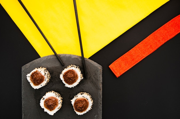 Placa de piedra negra con rollos de sushi sobre un fondo negro