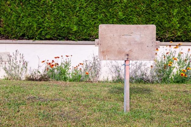 Placa de piedra rectangular contra el fondo de la pared de hiedra. tablero de la muestra vacía con borde, marco. marco conceptual, lugar para texto, placa con copyspace