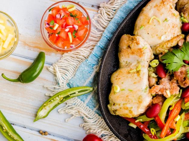 Placa de pollo frito con verduras y salsa.