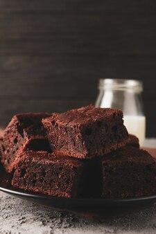 Placa con rebanadas de pastel de chocolate y una botella de leche en gris, de cerca