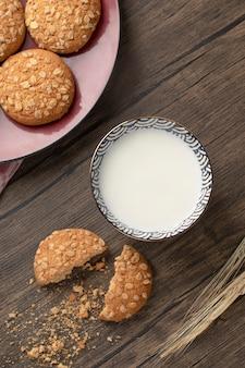 Placa roja con galletas de avena y tazón de leche fresca en la mesa de madera