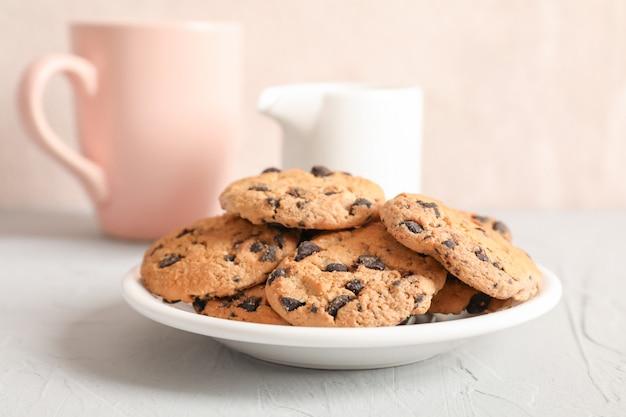 Placa con sabrosas galletas de chispas de chocolate y una taza de leche borrosa sobre fondo gris, primer plano