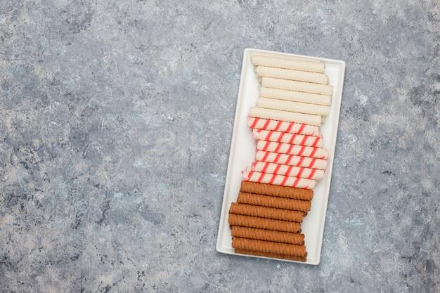 Placa con sabrosos palos de obleas sobre superficie de hormigón