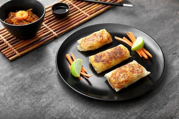 Placa con sabrosos rollitos de primavera fritos en mesa