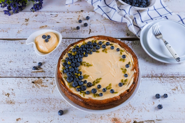 Placa con tarta de queso de arándanos decorada en la mesa