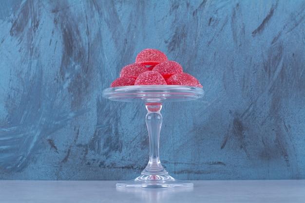 Una placa de vidrio llena de caramelos de gelatina de frutas azucaradas rojas sobre fondo gris. foto de alta calidad