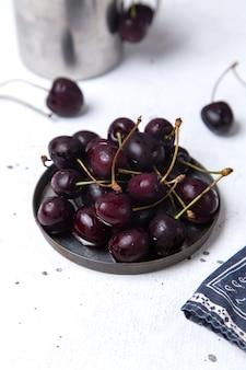 Placa de vista frontal con cerezas oscuras frescas agrias y suaves en jugo fresco de frutas blancas