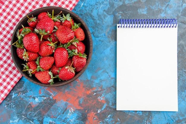 Placa de vista superior con fresas frescas frutas maduras sabrosas con bloc de notas sobre fondo azul.