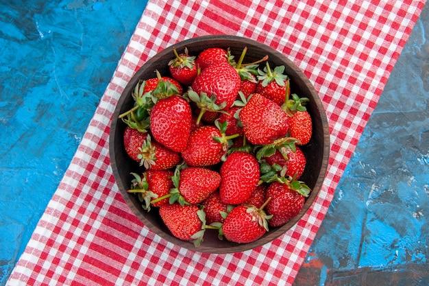 Placa de vista superior con fresas frescas frutas maduras sabrosas sobre fondo azul.