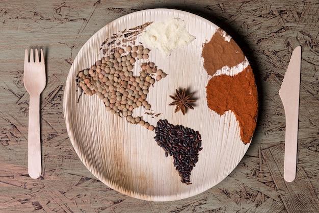 Placa de vista superior con mapa del mundo y frijoles