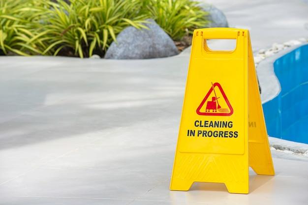 Placas de advertencia de limpieza en progreso al lado de la piscina