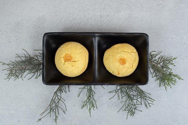 Placas oscuras con dos galletas dulces redondas sobre superficie blanca.