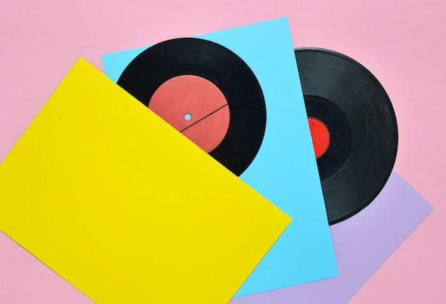 Placas de vinilo sobre una superficie en colores pastel. atributos musicales retro de los años 80. vista superior, minimalismo. copia espacio