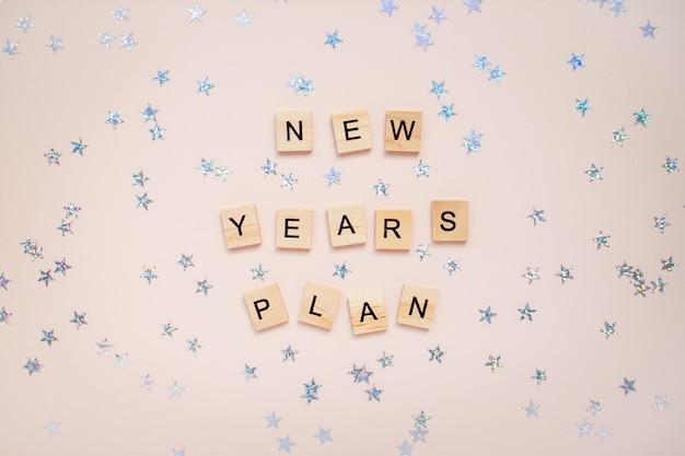 El plan de año nuevo de inscripción de bloques de madera con estrellas plateadas