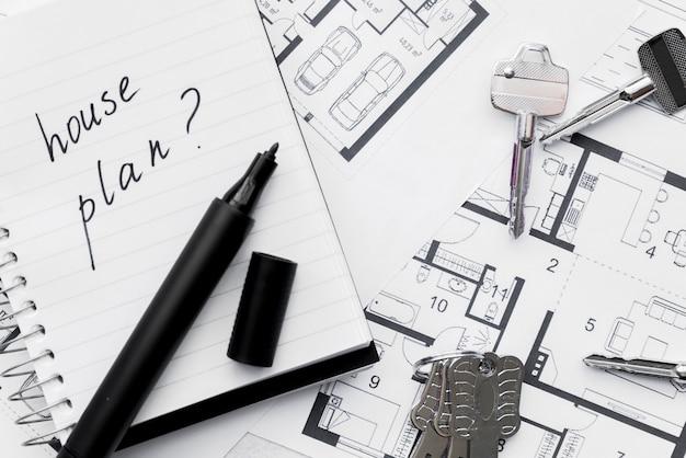 Plan de la casa con el signo de interrogación escrito en el cuaderno con rotulador y llaves en el plano azul