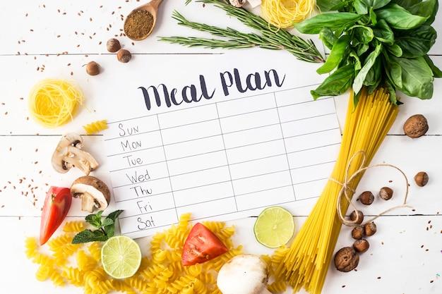 Un plan de comidas para una semana en una mesa blanca entre productos para cocinar.