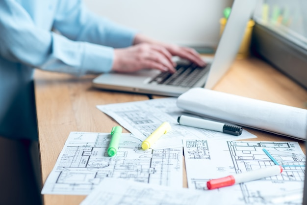 Plan de construcción en el alféizar de la ventana y manos femeninas cerca de la computadora portátil