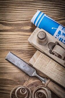 Plan de construcción azul cepilladora cincel plano espárragos de madera virutas sobre tablero de madera vintage