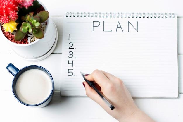 Plan en cuaderno, cactus y taza de café.