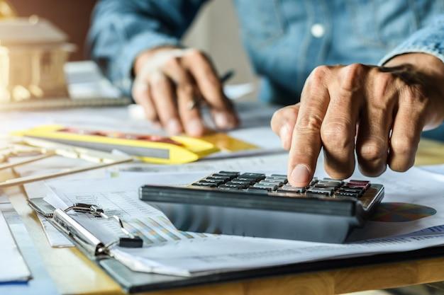 Plan de inspección de trabajo ingeniero esbozo en el lugar de trabajo con el uso de la calculadora