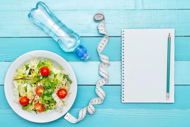 Plan de dieta, menú o programa, cinta métrica, agua y comida dietética.