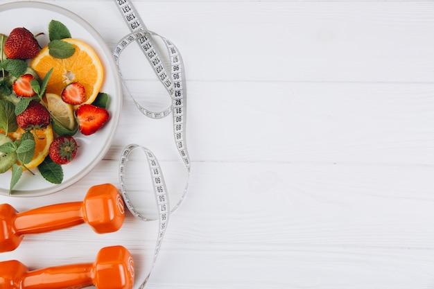 Plan de dieta, menú o programa, cinta métrica, agua, pesas y comida dietética de frutas frescas en blanco