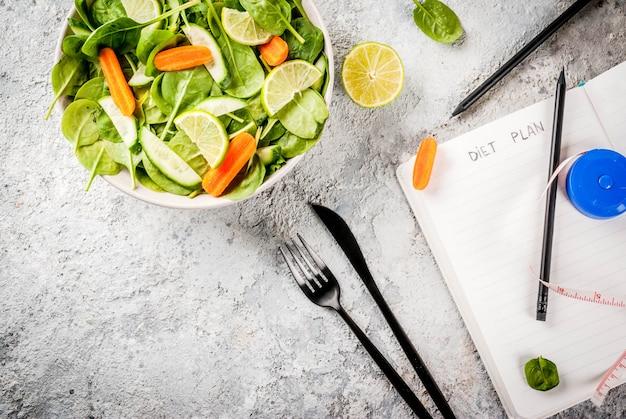 Plan de dieta para perder peso concepto ensalada de verduras frescas con tenedor cuchillo cuaderno de notas mesa de piedra gris