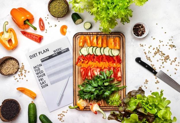 Plan de dieta y verduras frescas picadas sobre tabla de madera.