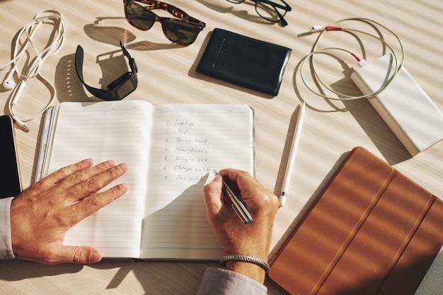 Plan de escritura de hombre irreconocible en diario y gadgets tirados en el escritorio