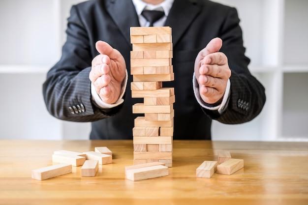 El plan y la estrategia en los negocios protegen con equilibrio la pila de madera