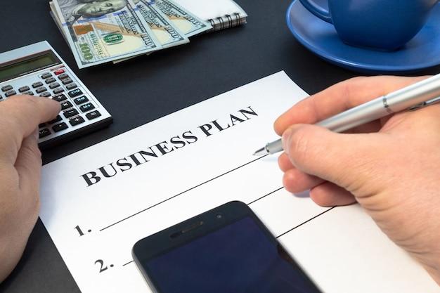 Plan estratégico de negocios con café, bolígrafo y mano en mesa negra