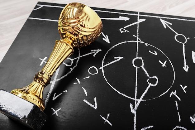 Plan de fútbol pizarra con táctica de formación y trofeo