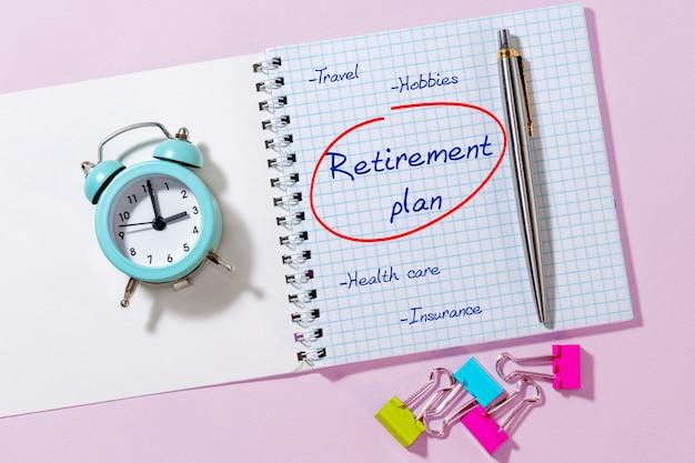 Plan de jubilación en un bloc de notas abierto con un bolígrafo y un reloj despertador.