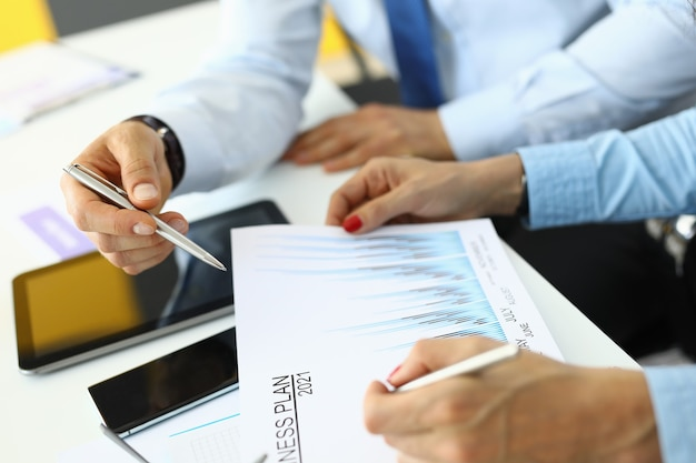 Plan de negocios para 2021 tablet smartphone y manos con bolígrafos. establecer objetivos comerciales para el concepto del próximo año