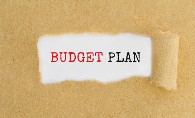 Plan de presupuesto de texto que aparece detrás de papel marrón rasgado.