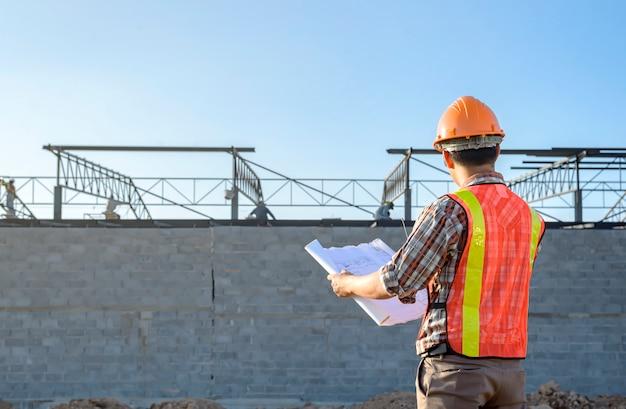 Un plan de trabajador de construcción que verifica el área del sitio de construcción durante las horas de trabajo